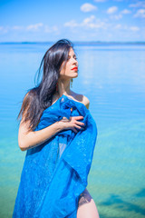 A woman in blue fabrics poses on the shore of the water, relaxes and shows herself in all its glory demonstrating a beautiful and well-proportioned figure