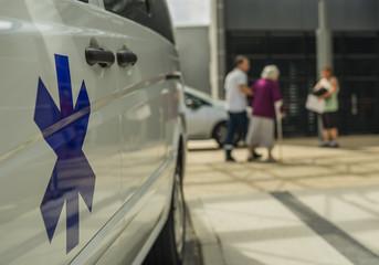 Ambulance avec étoile de vie devant un hopital et senior avec béquille – Krankenwagen mit Star of life vor Krankenhaus und Seniorin mit Gehhilfe