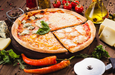 Classic Italian Four Cheese Pizza with Mozzarella, Brie, Dor Blue, Radamir on a dark wooden background with ingredients around (close top view). Cut one piece