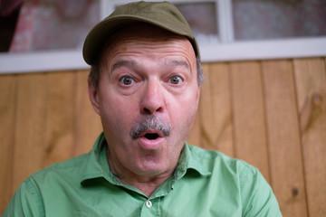 portrait of a mature man in cap surprised