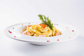Creamy pasta. Fettuccine with salmon fillet in a mild cream sauce with red caviar (close)