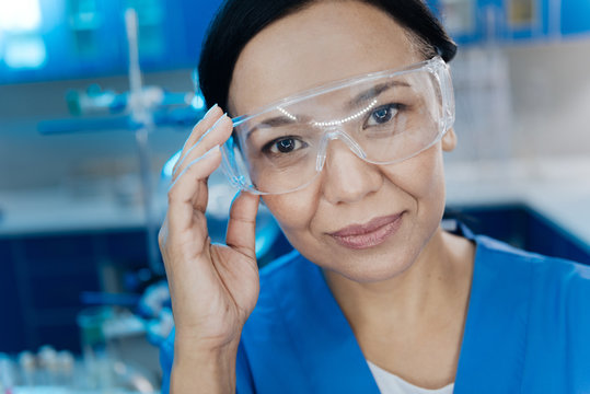 Cheerful attractive woman holding her protective glasses