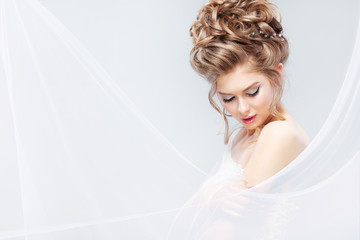 Beautiful bride with fashion wedding hairstyle - on gray background. Closeup portrait of young gorgeous bride. Wedding. Studio shot with copy space. Beautiful bride portrait with veil over her face