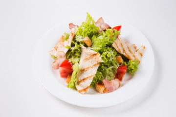 salad with bacon, tomatoes and croutons on a white plate