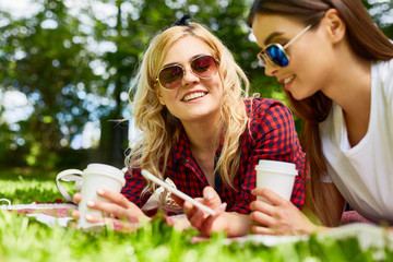 Portrait of two beautiful young girls enjoying picnic in sunny park laying on blanket with coffee cups