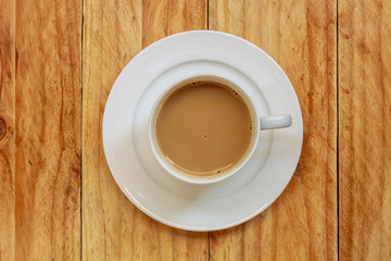 Coffee cup on wooden table, Top view.