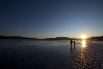 Silhouettes of two kids walking on frozen Lake Pend Oreille at sunset