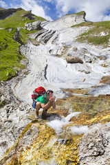 A hiker is splashing cold water to his face, on a spectacular rock formation near the Col des Fours above la Ville des Glaciers.