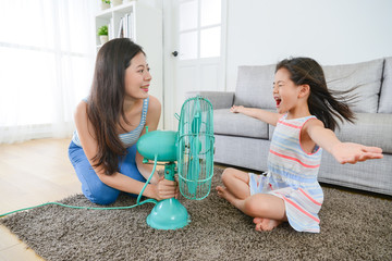 mother using fan let daughter enjoying cool wind