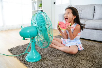 beautiful girl sitting in front of electric fan