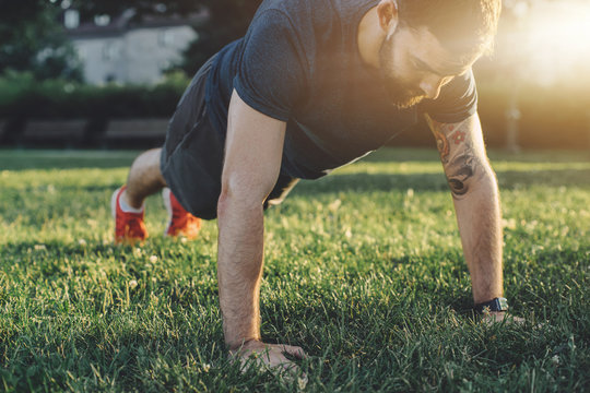 Young man exercising push up outside in sunny park, Sport fitness man doing push-ups