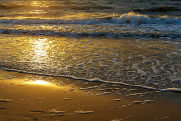 The rays of the sunset reflects on a sea waves