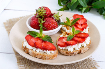 Delicious healthy dietary breakfast: rye bread with cottage cheese and strawberries  on a white wooden background.