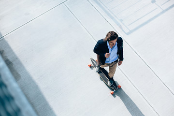 Young businessman going to work on a skateboard