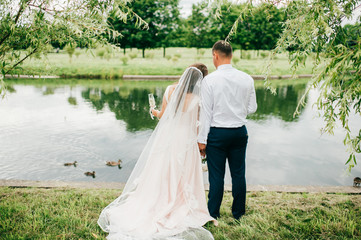 Bride with groom standing beyond river and looking forward.  Wedding day celebration at nature. Hands holding each other. Just married. Wife in dress and husband in suit with glasses of champagne.