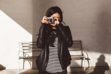Playful woman taking pictures with a digital camera