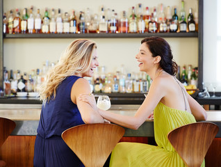 Girlfriends hanging out at lounge in a bar and restaurant having drinks