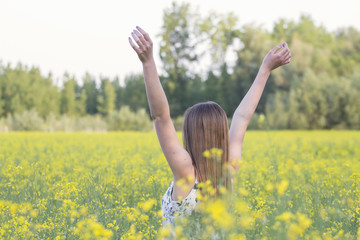 Young girl in the middle of the field with hands up
