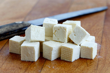 Cubes of cut white tofu and rustic knife on wooden chopping board.