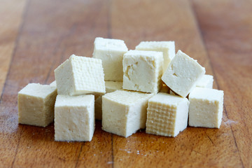 Cubes of cut white tofu on wooden chopping board.