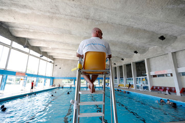 A lifeguard watches over swimmers at the Marville indoor swimming pool in Saint-Denis which is part of the Marville sports complex, northern Paris