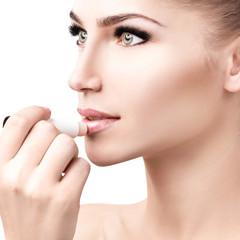 Beautiful woman applying hygienic lip balm.