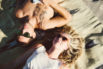 Young beautiful couple lays on a beach blanket listening to music together on their phone.