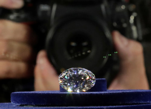 A photographer takes a picture of the main 51.38-carat diamond on display during Russian miner Alrosa's presentation of the Dynasty polished diamonds collection in Moscow