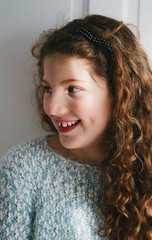 A little girl with long curly hair looking away from camera and smiling.