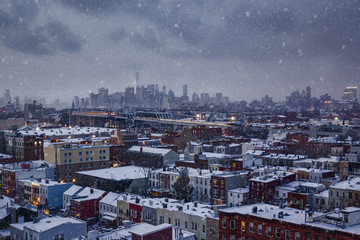 Snowy New York - Lower Manhattan skyline over Brooklyn apartment rooftops
