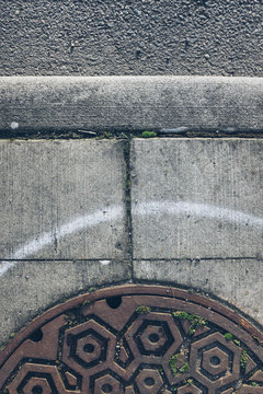 Sewer cap and white painted line on urban sidewalk, close up
