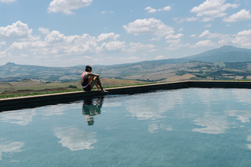 Girl dipping her toe into a still swimming pool in Tuscany, Italy.