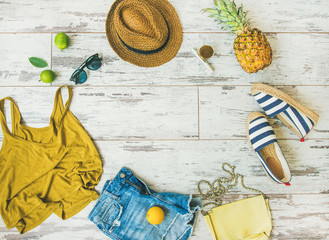 Wall Mural - Colorful summer fashion outfit flat-lay. Denim shorts, straw sun hat, yellow top, espadrillas, leather bag, sunglasses, pineapple, limes and lemon over pastel parquet background, top view, copy space