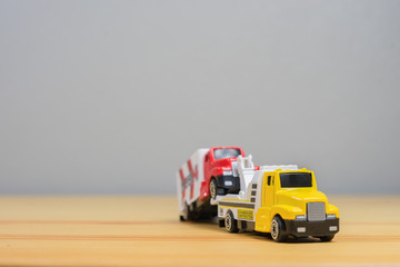 Loading broken toy car on a service tow truck  on a roadside after acident on grey background.copy space