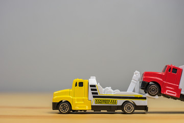 Loading broken toy car on a service tow truck  on a roadside after acident on grey background.
