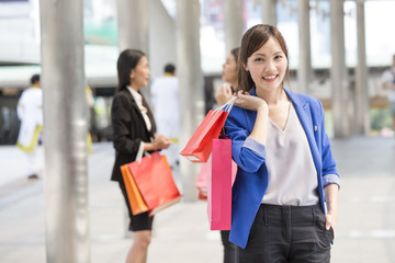 Asian Woman holding Shopping bag with Attractive smile at city. Woman shopping concept.