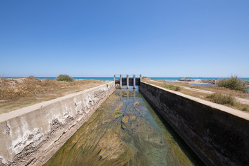 canal waterway river towards Mediterranean Sea with open ancient sluices, next to Gurugu Beach in Castellon, Valencia, Spain, Europe. Blue clear sky