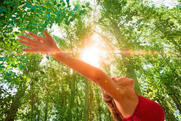 Mujer con los brazos abiertos en paisaje con arboles.Puesta de sol en paisaje de ensueño.Concepto de felicidad y paz espiritual.