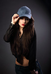 Beautiful sexy young make-up model in blue baseball cap with red lipstick posing on dark black background