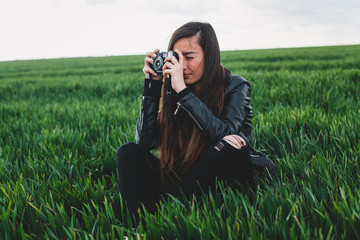 Young woman taking pictures with camera on green grass field