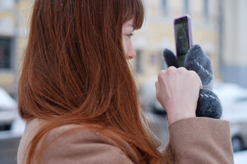 Young redhead woman taking photo with her smartphone