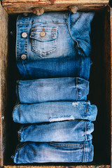 Selection of blue denim clothing in a wooden box