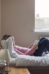 Girl reading a book while lying on a bed