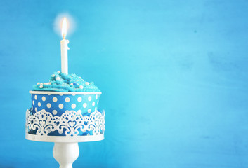 Birthday concept with cupcake and one candle on wooden table