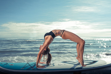 Beautiful sporty woman practicing SUP yoga at sunrise.