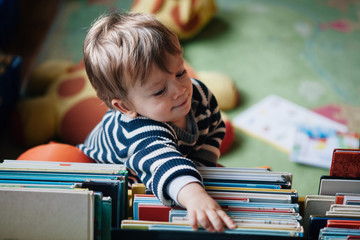 Cute baby boy picking a book in a children library