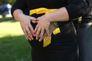pregnant lady in black dress with yellow ribbon