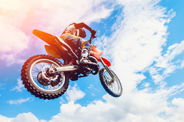 racer on a motorcycle participates in motocross in flight, jumps and takes off on a springboard against the sky. Concept active extreme rest. Fototapete