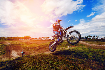 racer on mountain bike participates in motocross race, takes off and jumps on springboard, against the background of the participants. Close-up. concept of extreme rest, sports racing. ray of light