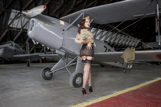 Beautiful redhead girl dressed in style pinup of the second world war, next to a military plane
